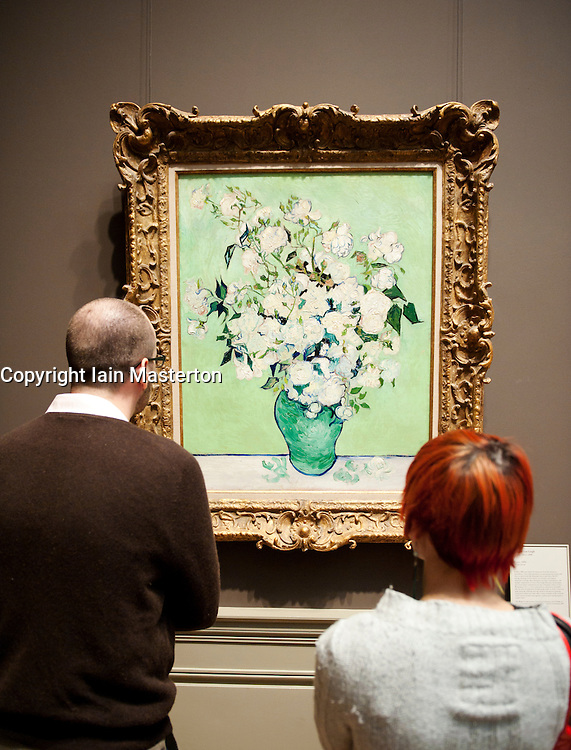 Visitors looking at painting Roses by Vincent van Gogh at the Metropolitan Museum of Art in Manhattan , New York City, USA