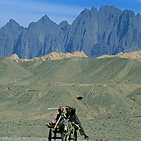A Uygar villager from Mingyol steers a burro cart carrying his wife and him to a market town below the arid Kara Tagh Mountains on the edge of the Taklimakan Desert near Kashgar (Kashi) in Xinjiang, China.