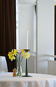 A restaurant table with a white linen table cloth and a yellow Easter daffodil lily flower and candle on the table. against a white background Ulriksdal Ulriksdals Wärdshus Värdshus Wardshus Vardshus Restaurant, Stockholm, Sweden, Sverige, Europe