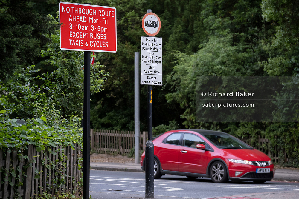 A car passes the signpost at the junction of the South Circular (A205) and College Road in Dulwich Village, warning motorists of the restrictions preventing traffic from passing through at morning and afternoon rush-hour times in the borough of Southwark, on 15th June 2021, in London, England.