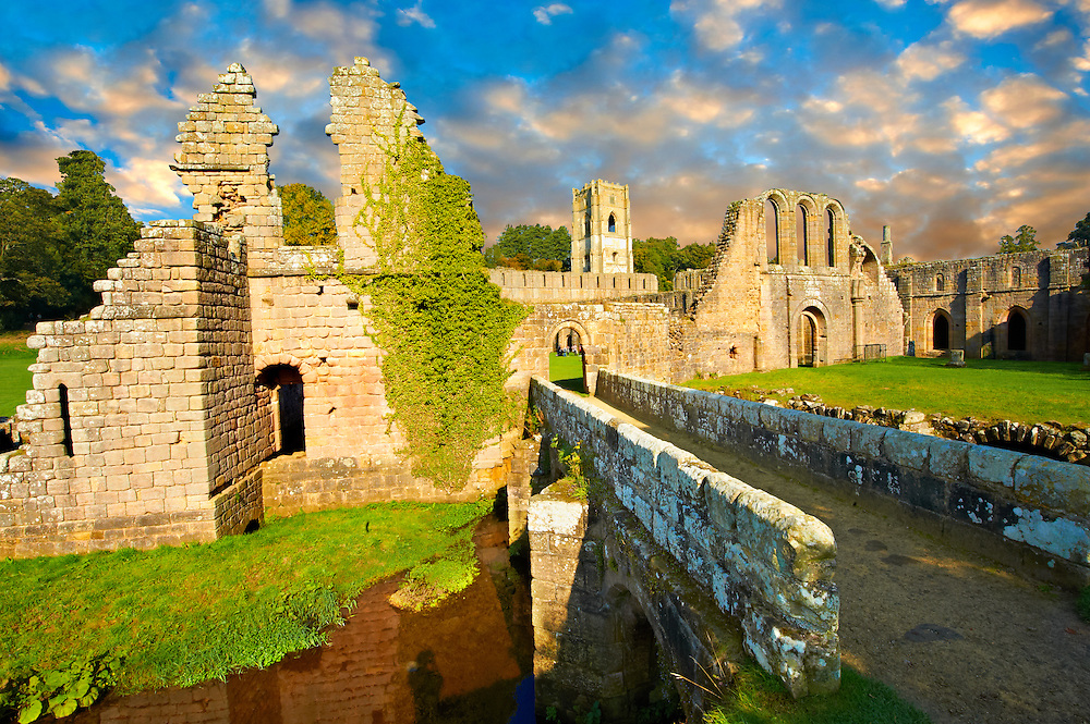 Entrance at sunrise  of the ruins of Fountains Abbey , founded in 1132, is one of the largest and best preserved ruined Cistercian monasteries in England. The ruined monastery is a focal point of England's most important 18th century Water, the Studley Royal Water Garden which is a UNESCO World Heritage Site. Near Ripon, North Yorkshire, England .<br /> <br /> Visit our MEDIEVAL PHOTO COLLECTIONS for more   photos  to download or buy as prints https://funkystock.photoshelter.com/gallery-collection/Medieval-Middle-Ages-Historic-Places-Arcaeological-Sites-Pictures-Images-of/C0000B5ZA54_WD0s