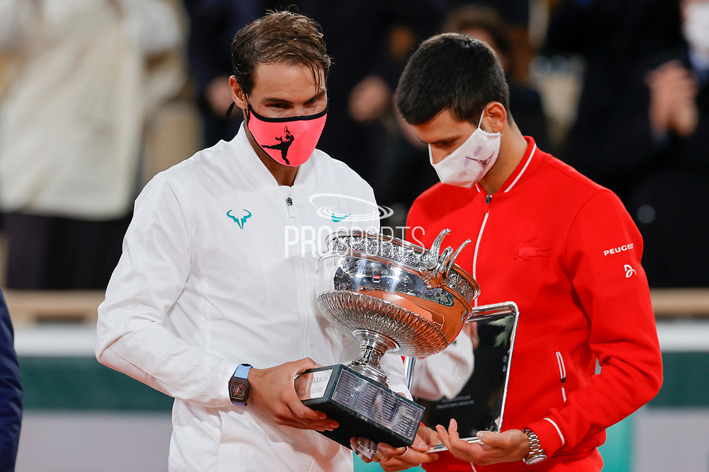 RAFAEL NADAL (ESP) won his 100 th match and his 13 th Roland Garros, celebration with the trophy, NovakDJOKOVIC (SRB) in the background during the Roland Garros 2020, Grand Slam tennis tournament, women single final, on October 9, 2020 at Roland Garros stadium in Paris, France - Photo Stephane Allaman / ProSportsImages / DPPI