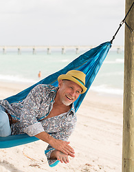 handsome middle aged man enjoying time on a hammock at the beach