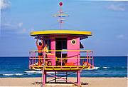 A fit-looking Miami Beach lifeguard stands on a Post-Modern lifeguard station designed by architect William Lane and pop artist Kenny Scharf. <br /> <br /> Their design takes Naurical Moderne elements -- such as the porthole windows and metal railings -- from Miami Beach's Art Deco past, and combines them with a spacey and playful Jetsons cartoon-like  sensibility, as seen in the decorative antenna-like finial and the bright pink and yellow paint job.