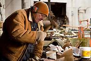 male senior blacksmith hammering hot metal