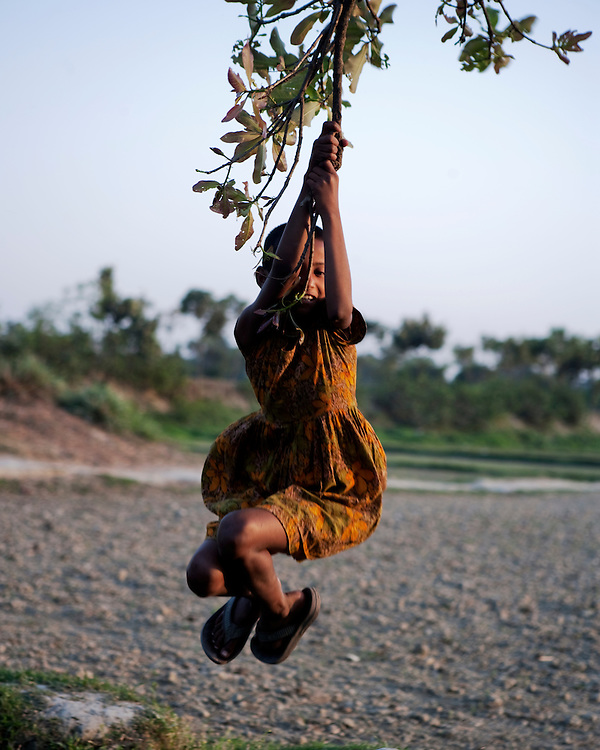 Girl playing swinging from a branch of a tree