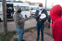 A member of the LEAN team hands out masks to commuters in a taxi at a Mayville taxi rank.