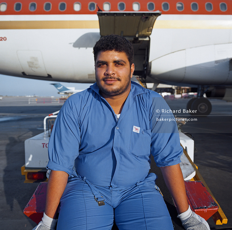 A Bahrani baggage-handler employed by SABTCO pauses during his shift at Bahrain International airport. Having loaded luggage and cargo into the hold of an Egyptair Airbus, he sits looking hot and tired on the company?s conveyor belt awaiting last-minute additions to the manifest before its imminent departure for Cairo, across the Mediterranean. It is another hot day in this Gulf State, a key hub airport in the region, providing a gateway to the Northern Gulf. The airport is the home for Gulf Air which provides 52% of overall movements and is also the half-way point between Western Europe and Asian destinations such as Hong Kong and Beijing. Picture from the 'Plane Pictures' project, a celebration of aviation aesthetics and flying culture, 100 years after the Wright brothers first 12 seconds/120 feet powered flight at Kitty Hawk,1903.