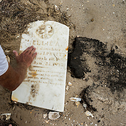 "August 4, 2017 - Tangier Island, VA - Old gravestones frequently are unearthed on the part of Tangier Island known as ""The Uppards."" Here, Mayor James ""Ooker"" Eskridge wipes off sand from one of his wife's ancestors (Pruitts) gravestones on the island.  The Uppards was a previously habited portion of Tangier Island that is today very diminished in size due to erosion.  A few of the old homes from this area of the island have been moved to the more inhabited part of the island, across a widening waterway once accessible by bridge. That bridge no longer exists<br /> <br /> Photo by Susana Raab/Institute"