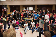 Friends and family take photos of the Iraan High School football team and a cake decorated with the bus the team will take to Arlington and the trophies they plan to win during a community dinner in Iraan, Texas on December 13, 2016. (Cooper Neill for The New York Times)