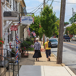 Strasburg, PA / USA - June 26, 2011: Two women walking on the sidewalk in the quaint, Lancaster County borough in the summer.