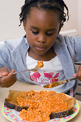 Young girl tucking into a plate of beans on toast,