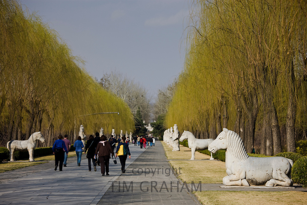 Tourists walk past horse statues on Spirit Way at the Ming Tombs site, Beijing (Peking), China