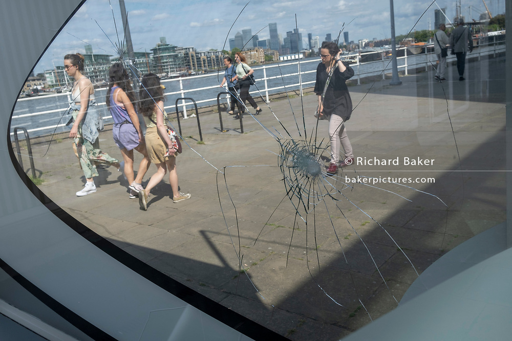 Passers-by walk through sunlight with the impact marks from vandalised glass at Butler's Wharf, on 11th June 2021, in London, England.