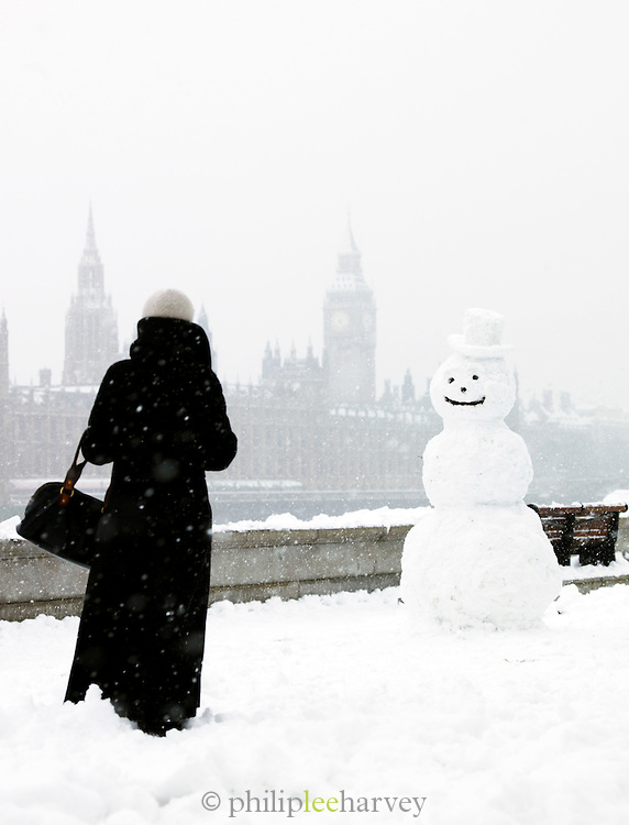A woman with a snowman on the south bank on the River Thames opposite Big Ben and the Houses of Parliament, London, UK