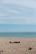 A topless man asleep on a pebble beach on the 2nd June 2019 in Eastbourne in the United Kingdom. Eastbourne is a resort town on England's southeast coast.