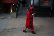 A young girl dressed in red looks at her mobile phone while walking on 19th February 2017 in London, United Kingdom. From the series Our Small World, an observation of our mobile phone obsessions