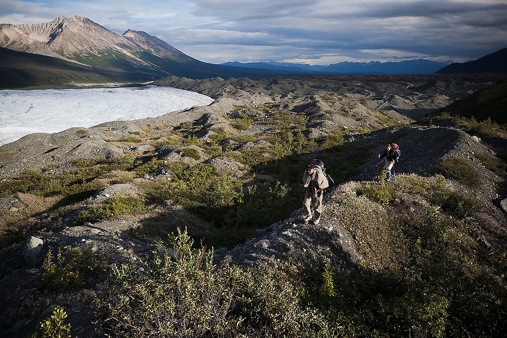 Parmenter and Liana Welty hike up the lateral moraine on the west side of the Root Glacier on a backpacking trip to Donoho Basin, Wrangell-St. Elias National Park, Alaska.