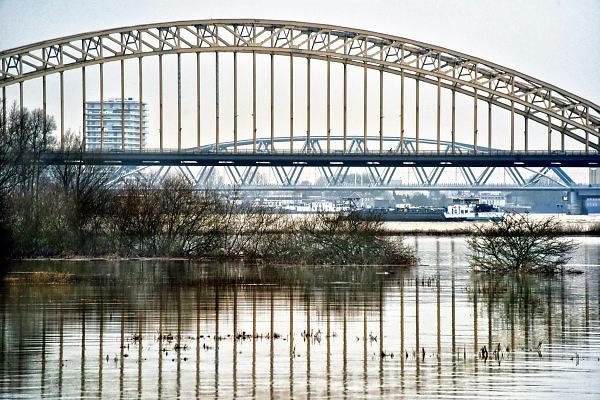 Nederland, Nijmegen, 12-1-2018Het hoogwater, hoge water, trekt veel nieuwsgierigen en andere dagjesmensen naar de Ooijpolder en levert schilderachtige beelden op. De Waalbrug refecteerd in de stilstaande watermassa van de overstroomde, ondergelopen uiterwaarden. De scheepvaart verderop op de rivier heeft de hele hoogwaterperiode door mogen varen.Foto: Flip Franssen