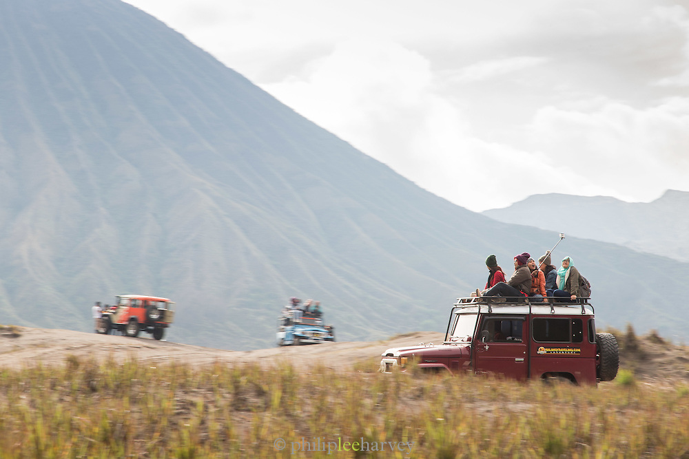 Tourist on roofs of Toyota Land cruisers, foot of Mount Bromo, Mount Bromo Crater, Mt Bromo, Tengger massif, East Java, Indonesia, Southeast Asia