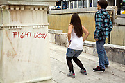 Teenagers dance in front of a statue in Syntagma Square daubed with graffiti reading 'fight now', Athens, GreeceTeenagers dance in front of a statue in Syntagma Square, Athens, Greece