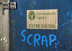 """© London News Pictures. 31/01/2014. Burrowbridge, UK. Graffiti reading """"SCRAP"""" written next to a sign for the Environment Agency in the village of Burrowbridge in Somerset on the Somerset levels.  The area has been hit severely by recent flooding which is forecast to get worse over the weekend . Photo credit: Jason Bryant/LNP"""