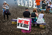 The instructions Dont Drive On The Grass seems ironic after total destruction of the pasture surrounding the Glade area of the 2016 Glastonbury Festival. Heavy rain created a mud bath in the Shangri La camping field,  Glastonbury Festival 2016, United Kingdom. Glastonbury Festival is the largest greenfield festival in the world, and is now attended by around 175,000 people. Its a five-day music festival that takes place near Pilton, Somerset. In addition to contemporary music, the festival hosts dance, comedy, theatre, circus, cabaret, and other arts. Held at Worthy Farm in Pilton, leading pop and rock artists have headlined, alongside thousands of others appearing on smaller stages and performance areas.