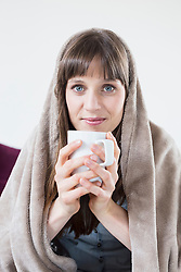 Portrait of mid adult woman covered with blanket and holding cup of tee