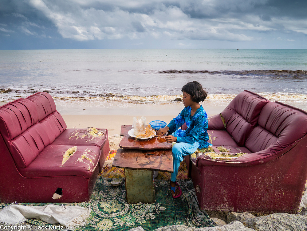 04 NOVEMBER 2012 - KAO SENG, SONGKHLA, THAILAND:  A girl makes her family's lunch on a living room set on the beach in Kao Seng. Kao Seng is a traditional Muslim fishing village on the Gulf of Siam near the town of Songkhla, in the province of Songkhla. In general, their boats go about 4AM and come back in about 9AM. Sometimes the small boats are kept in port because of heavy seas or bad storms.    PHOTO BY JACK KURTZ