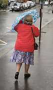 middle aged woman holding her umbrella to protect against wind and rain