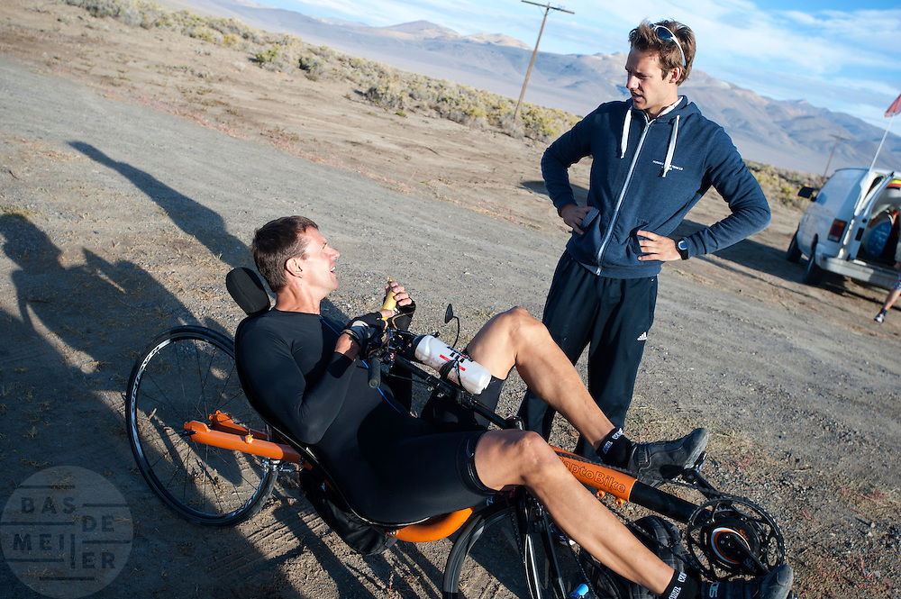 Wil Baselmans praat met trainer Jeroen na afloop van de ochtendwedstrijd op de vierde dag van de WHPSC. In Battle Mountain (Nevada) wordt ieder jaar de World Human Powered Speed Challenge gehouden. Tijdens deze wedstrijd wordt geprobeerd zo hard mogelijk te fietsen op pure menskracht. Ze halen snelheden tot 133 km/h. De deelnemers bestaan zowel uit teams van universiteiten als uit hobbyisten. Met de gestroomlijnde fietsen willen ze laten zien wat mogelijk is met menskracht. De speciale ligfietsen kunnen gezien worden als de Formule 1 van het fietsen. De kennis die wordt opgedaan wordt ook gebruikt om duurzaam vervoer verder te ontwikkelen.<br /> <br /> The morning runs on the fourth day of the WHPSC. In Battle Mountain (Nevada) each year the World Human Powered Speed Challenge is held. During this race they try to ride on pure manpower as hard as possible. Speeds up to 133 km/h are reached. The participants consist of both teams from universities and from hobbyists. With the sleek bikes they want to show what is possible with human power. The special recumbent bicycles can be seen as the Formula 1 of the bicycle. The knowledge gained is also used to develop sustainable transport.
