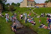 Hutton Le Hole, picturesque village on the Yorkshire moor, England, UK.<br /> Summer visitors by the stream.