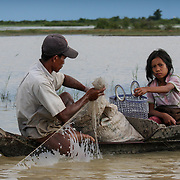 Father and daughter pull fishing net into wooden canoe (Siem Reap, Cambodia - Oct. 2008) (Image ID: 081023-1548161a)