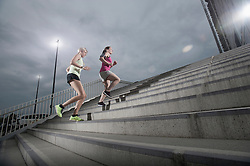 Two women jogging on staircases during dawn, Bavaria, Germany