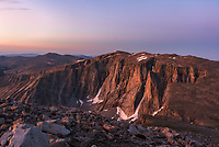 Every summer I try to climb at least one big mountain, and this time it was Darton Peak. It's one of the highest peaks in the Bighorns, and is very prominent from Highway 16 far below. With a goal of standing on the summit at sunrise, that meant a 3:30AM wake up time. But the bright moonlight helped illuminate my route as the stars faded out. The wind chill up here was in the lower 20's and fresh snow lingered from a couple days earlier despite it being August. Darton is typical of other peaks in the Bighorns and is covered with car-sized boulders. With towering cliffs on 2 sides, the long and rounded peak requires a 16 mile roundtrip hike, but I was able to camp at Lost Twin Lakes the night before. At an elevation of 12,275 feet, the air is only 63% of what it is at sea level. There's always something beautiful about the way the the light appears at high altitudes at the edge of day. It's amazing how the colors can seem both soft and intense at the same time.This view is looking south towards Bighorn Peak.