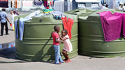South Africa - Cape Town - 08 October 2020 - 4 year old Hellen Ragasa playing with a boy while her mom speaks to a man in the background, she and her mother are part of the refugees at the refugee settlement at Paint City Bellville where they have been housed for the duration of the lockdown. The group of refugees from various countries in Africa has been protesting for a year, asking the UNHCR for assistance to leave South Africa because they fear for there safety and the safety of their families. Picture: Brendan Magaar/African News Agency(ANA)