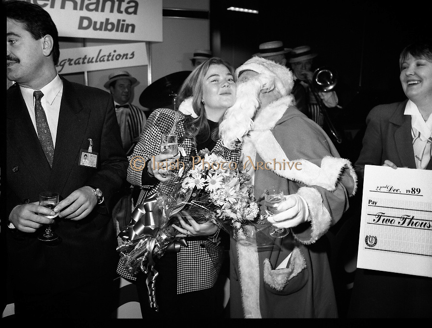 5,000,000th Passenger Through Dublin Airport. (T12).1989..22.12.1989..12.22.1989..22nd December 1989..The date,Friday,22nd December 1989 will be remembered as an historic day in Irish Aviation as Aer Rianta celebrated the 5millionth passenger to fly through Dublin Airport in one year. The Lucky passenger, Nicola Wynne, arrived at 10AM from Germany and was welcomed to Dublin Airport by General Manager,Tom Cullen...A happy nicola Wynne accepts a kiss of congratulations from Santa in Dublin Airport.