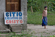 A boy by a sign outside  his home, Cubatão