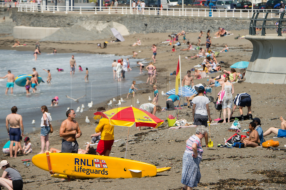 ©Licensed to London News Pictures. 25/07/2019. Aberystwyth, UK. People at the seaside in Aberystwyth  on yet another scorching  day as a plume of hot air continues to dominate the UK, with the likelihood of record breaking temperatures of 38 or 39ºc in parts of the south east this afternoon. Photo credit : Keith Morris/LNP
