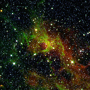 This image from NASA's Spitzer Space Telescope shows a wispy, vast structure in the constellation Perseus with a small bubble right in its center puffed out by the spasms of fresh-formed, heavyweight stars