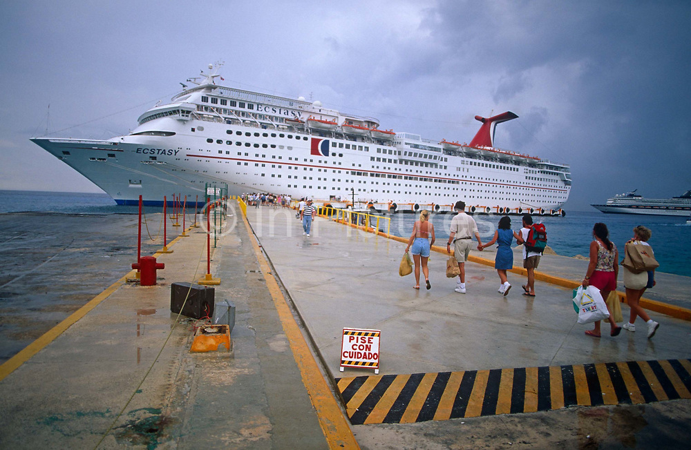 Largely American passengers re-join their cruise holiday voyage around the Gulf of Mexico during a day's stop-over in Cancun, Mexico. Walking back with shopping and tourist trinkets the holidaymakers walk along the port's quayside to have their identity passes checked before being allowed back on board the Fun Ship Ecstasy. The surface is wet and a warning sign in Spanish reads Walk with care and the pedestrians make their way back to their temporary home to continue their voyage. The Panamanian-registered MS Ecstasy is a 70,367 ton cruise ship carrying 2,052 passengers and 920 crew whose routes are mainly around the Gulf and Caribbean Sea.