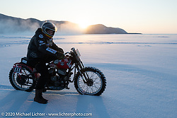 "Victor Dokuchaev on his 1942 WR 45"" Harley-Davidson Flathead racer checks out the setting sun from the middle of Lake Baikal during the Baikal Mile Ice Speed Festival. Maksimiha, Siberia, Russia. Friday, February 28, 2020. Photography ©2020 Michael Lichter."