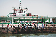 Port Said, Egypt - April 24, 2010: Several fishermen sit together at the ferry terminal in Port Said, Egypt