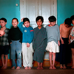 ULAAN BAATAR, MONGOLIA --4/01-- Children line up to await the order to eat in the Children's Identification Center in Ulaan Baatar.  Recently removed from the streets, they are clothed in whatever items the organization can find, which is given food and additional help by World Vision, a non-governmental organization, one of seventy working with the growing street people population in urban Mongolia...Copyright 2001 Susana Raab