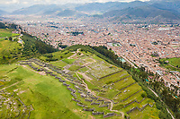 Aerial view of Cuzco city ruins, red rooftops and mountains, Peru.