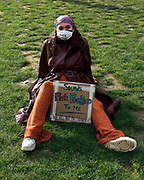 Protester sits on the grass, waiting for the event to begin with a sign opposing Priti Patel's new right to protest law. London. 15th March 2021.