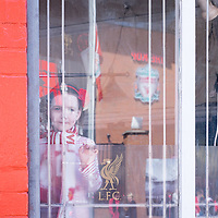 Anfield, Liverpool, UK. 15th April, 2014. A young Liverpool Football club fan  looks through a pub window at Anfield Stadium across the road.