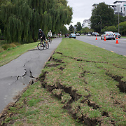 Cracks in a grass verge and cycle path in Christchurch after a Powerful earth quake ripped through Christchurch, New Zealand on Tuesday lunch time killing at least 65 people as it brought down buildings, buckled roads and damaged houses, churches and the Cities Cathedral. 23rd February 2011.  Photo Tim Clayton