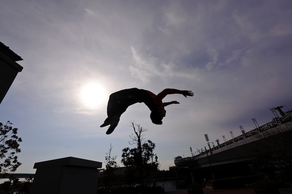 """Traceur (Parkour practitioner) Jun """"Sullivan"""" Sato executes a back flip. Practicing Parkour in Odaiba, Tokyo, Japan, January 27, 2012. Parkour is a modern method of physical training, also known as freerunning. It was founded in France in the 1990s. There is a small group of around 50 parkour practitioners in Tokyo."""