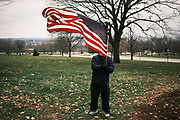 """06 DECEMBER 2020 - DES MOINES, IOWA: A supporter of President Donald Trump waves an American flag during a Trump motorcade at the Iowa State Capitol. About 1,000 supporters of outgoing US President Donald Trump rallied in Des Moines Sunday to show their support for the President and to protest the outcome of the US Presidential election. They started with a rally in the suburbs of Des Moines then drove in a motorcade through the city, ending at the State Capitol. They repeated many of Trump's discredited claims that the election was marked by fraud and that Trump actually won. The protest was a part of the national """"March for Trump"""" effort, culminating in a march in Washington DC on December 13. Joe Biden won the election, with 306 electoral votes to Trump's 232.       PHOTO BY JACK KURTZ"""